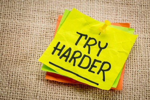 try harder - motivation words on a yellow sticky note against burlap canvas